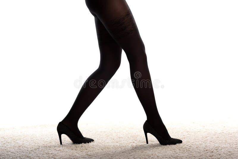 在高跟鞋和黑长袜的女性腿 免版税库存图片