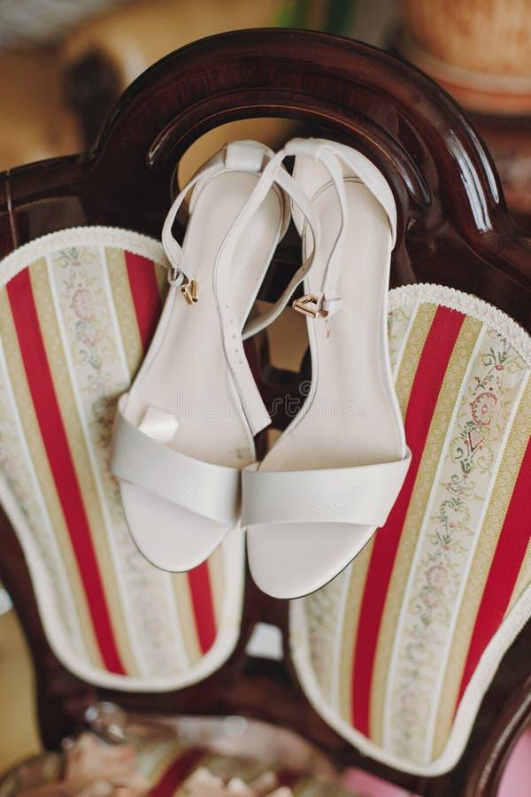 在高跟鞋在豪华椅子,在婚礼前的新娘闺房早晨细节的时髦的白色鞋子 免版税库存照片