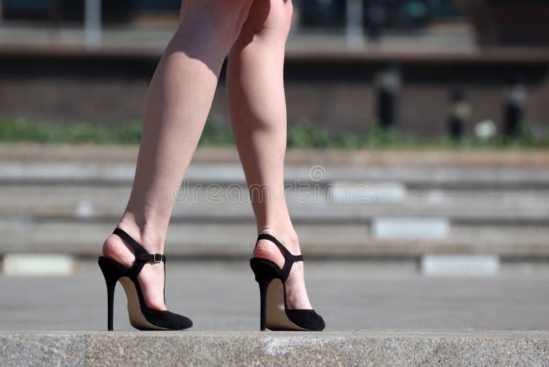 在高跟鞋,站立在街道上的凉鞋的亭亭玉立的妇女的性感的女性腿 免版税图库摄影