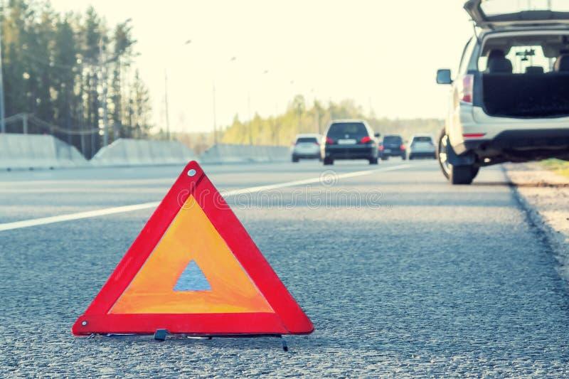 在高速公路和一个紧急刹车标志一边的残破的汽车 免版税图库摄影