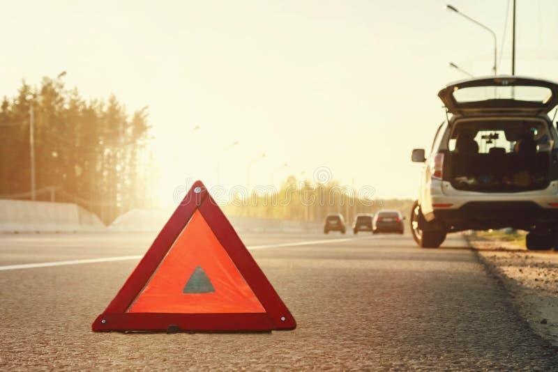 在高速公路和一个紧急刹车标志一边的残破的汽车 库存图片