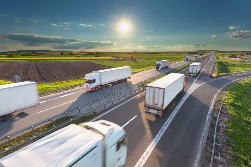 在高速公路的大白色卡车在田园诗晴朗的早晨 库存照片