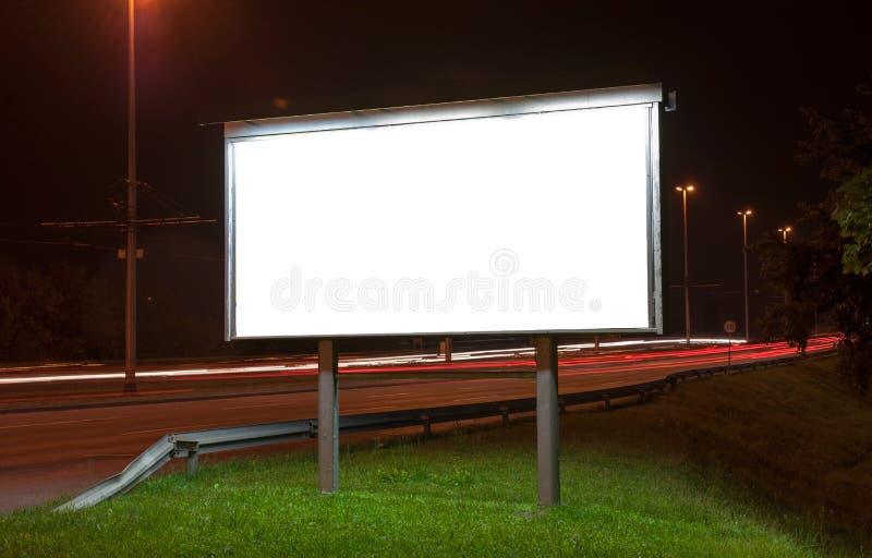 在高速公路的广告牌在夜之前 免版税库存照片