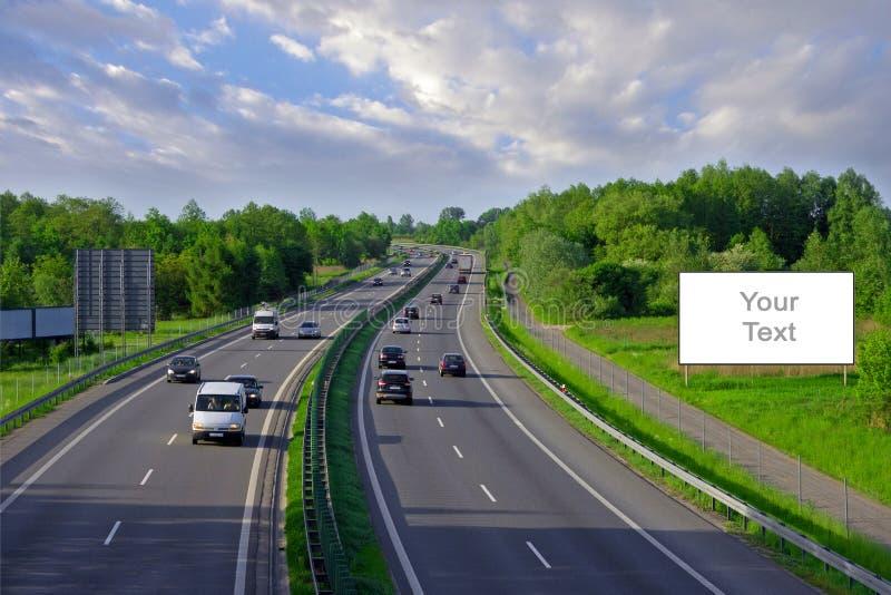 在高速公路的广告牌有许多的汽车 免版税库存照片