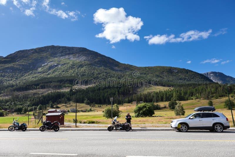 在高速公路路旁的三个摩托车和汽车身分在挪威的山的 旅行在斯堪的那维亚乘车 免版税库存照片