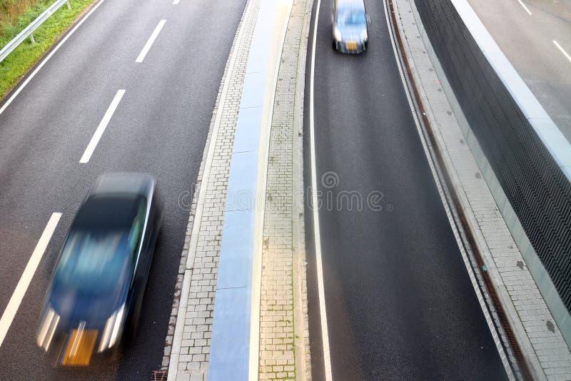 在高速公路车道的高速车 免版税库存照片