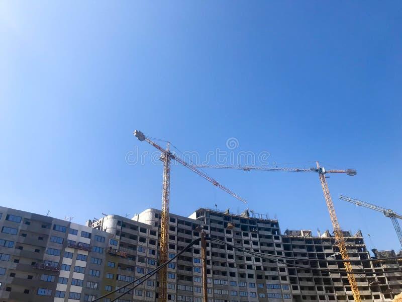 在高钢筋混凝土帮助下,盘区,塑象框架,框架块房子,大厦建筑用起重机的大厦  免版税库存图片