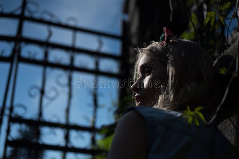 在高门后的侧视图害怕女孩佩带的头饰带身分在黄昏 有卷曲的金发的俏丽的少女 免版税库存图片
