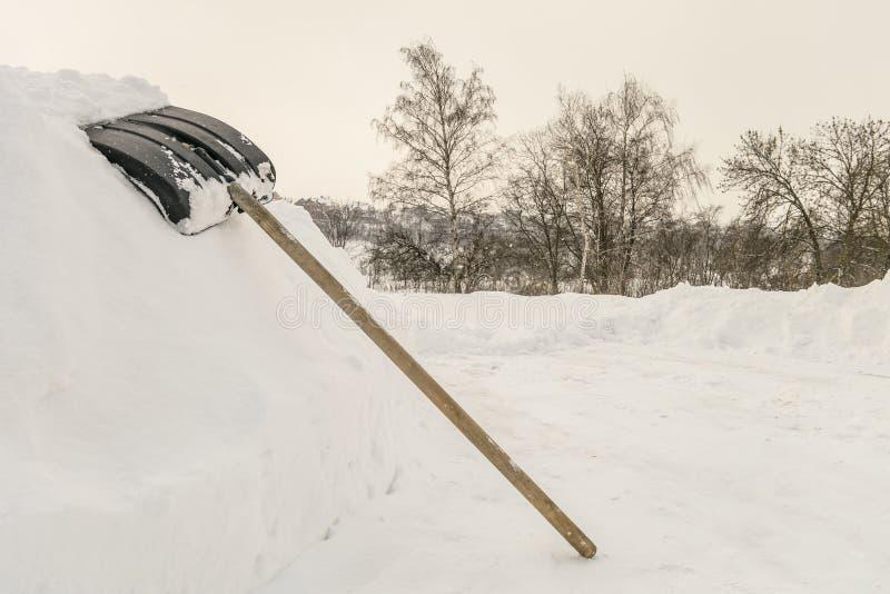 在高随风飘飞的雪的雪铁锹在乡下路附近 免版税库存图片