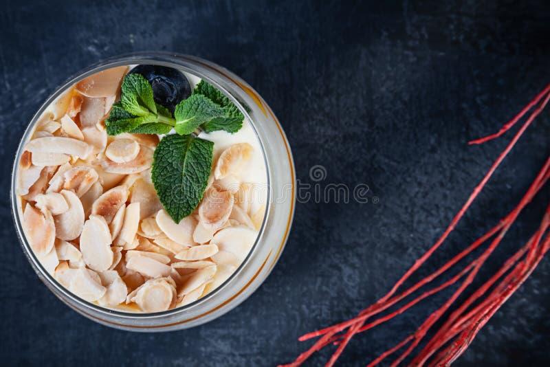 在鲜美提拉米苏的接近的看法与坚果和芒果 点心在与拷贝空间的黑暗的背景服务 菜单或食谱的图片 免版税图库摄影