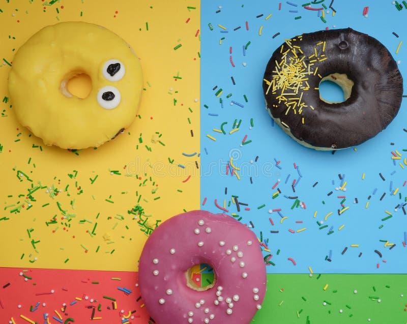 在鲜艳的多色背景上撒上洒水的圆形不同甜甜圈 库存照片