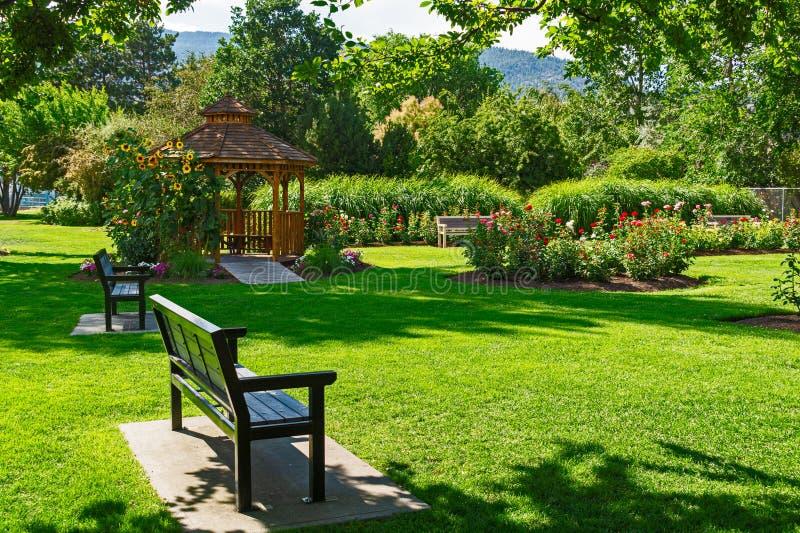 在鲜花盛开的向日葵下设有长椅和木制凉亭的休闲区 库存照片