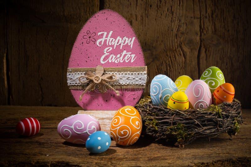 在鸟的五颜六色的被绘的愉快的复活节贺卡鸡蛋筑巢在土气木背景的篮子 库存图片