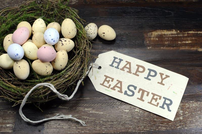 在鸟的愉快的复活节糖果复活节彩蛋在黑暗的葡萄酒与标记的被回收的木头筑巢 库存图片