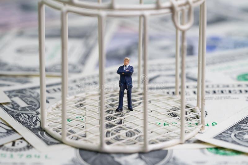 在鸟笼里面的微型商人在堆美元钞票 免版税库存照片