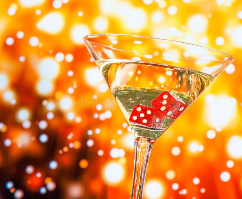 在鸡尾酒杯的红色模子在金黄bokeh 库存图片