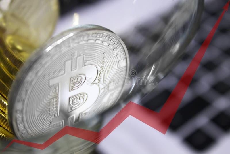 在鸡尾酒杯的金黄bitcoins,图表的红色箭头向上被指挥 免版税图库摄影