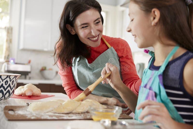 在鸡蛋面包面团的女孩掠过的釉与她的妈咪 免版税库存图片