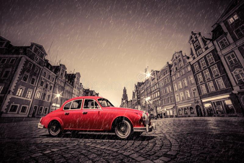 在鹅卵石历史的老镇的减速火箭的红色汽车在雨中 波兰wroclaw 免版税图库摄影