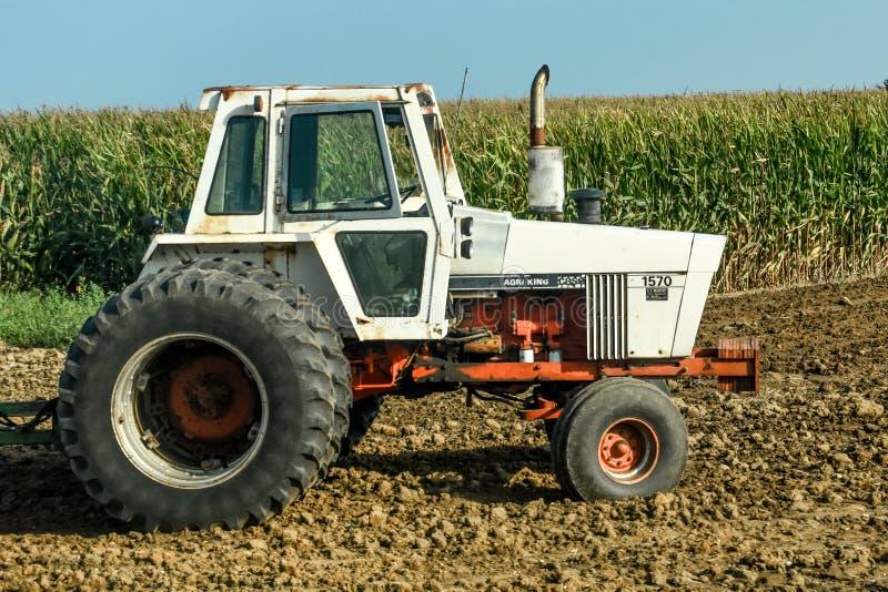 在麦地的白色农用拖拉机 库存照片