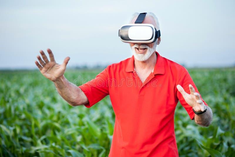 在麦地的资深农艺师或农夫身分和使用VR风镜 免版税库存图片