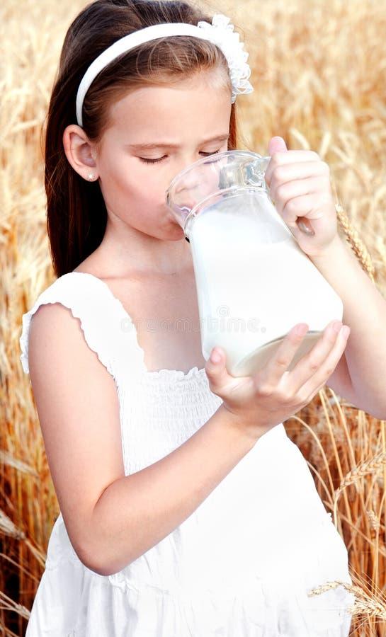 在麦田的可爱的小女孩饮用奶 免版税库存照片