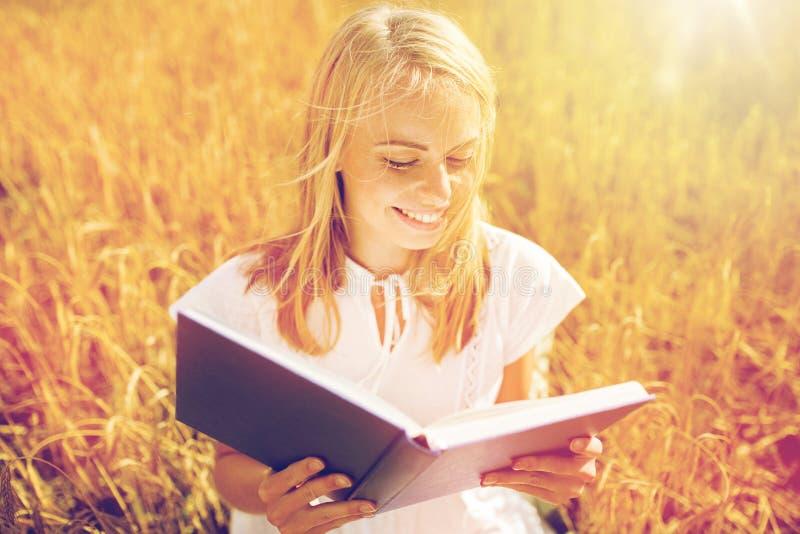 在麦田的微笑的少妇阅读书 免版税库存照片