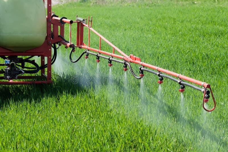 在麦田的拖拉机喷洒的除草药与喷雾器 免版税库存图片
