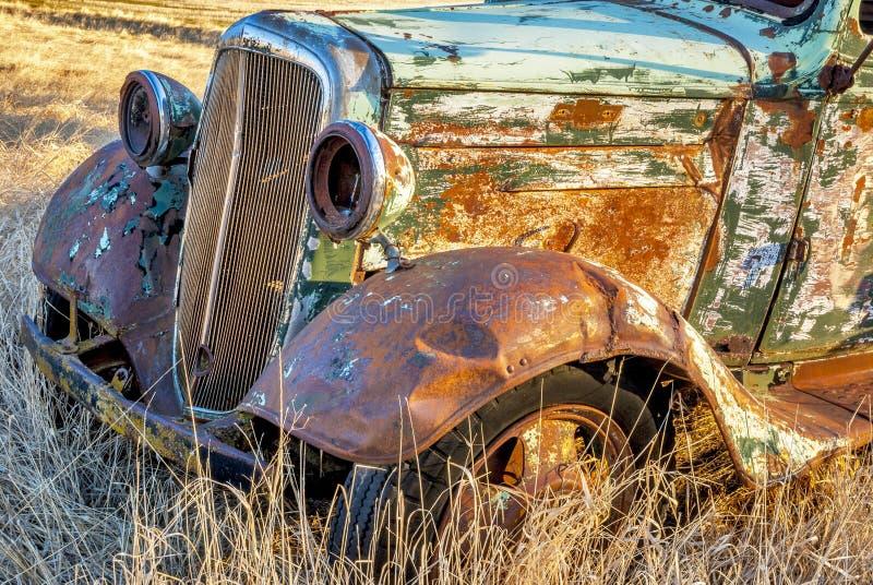 在麦田的生锈的老被忘记的卡车 库存照片