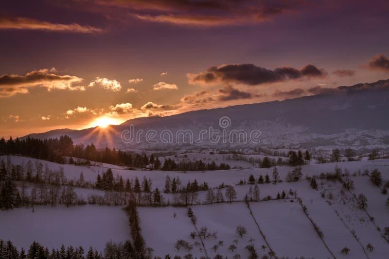 在麸皮的温暖和五颜六色的日落,从特兰西瓦尼亚的山村,盖用雪冬天 库存图片