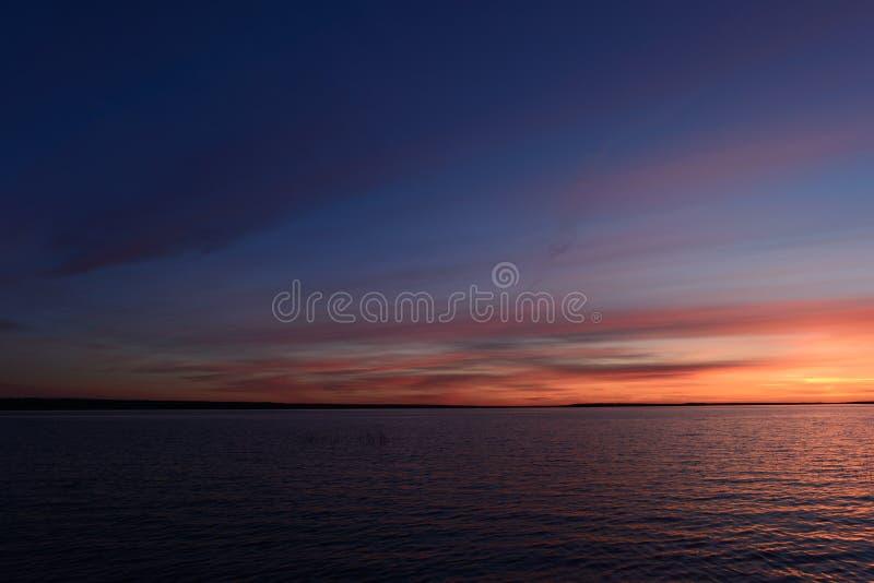在黄昏明亮的天空蔚蓝多云阴霾的暮色日落焕发在天际的在湖的水上 免版税图库摄影