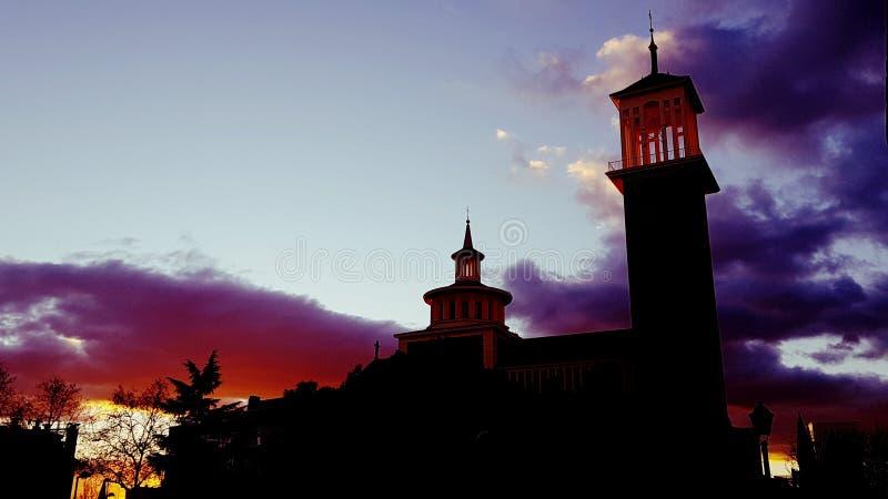 在黄昏的令人毛骨悚然的云彩作为日落在橙色光沐浴教会尖顶 免版税库存图片