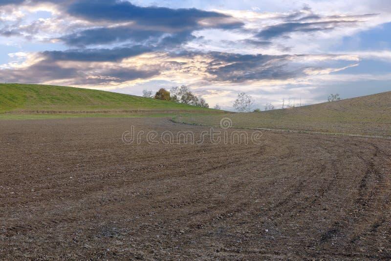 在黄昏的培养的被犁的领域在多云天空下 库存照片