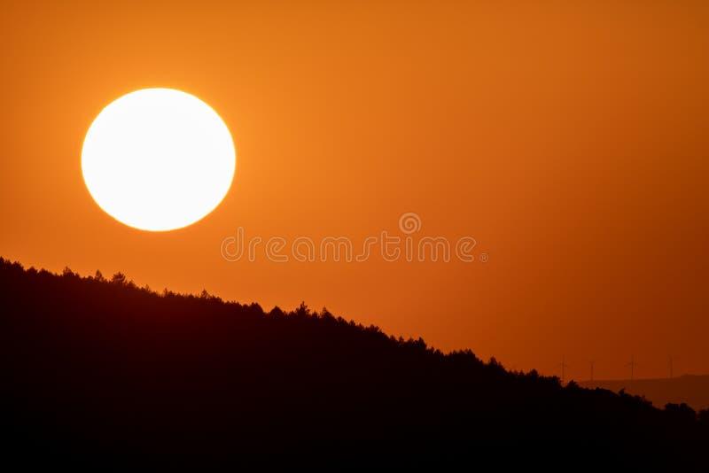 在黄昏的大太阳圈子在与橙色天空的山 库存照片