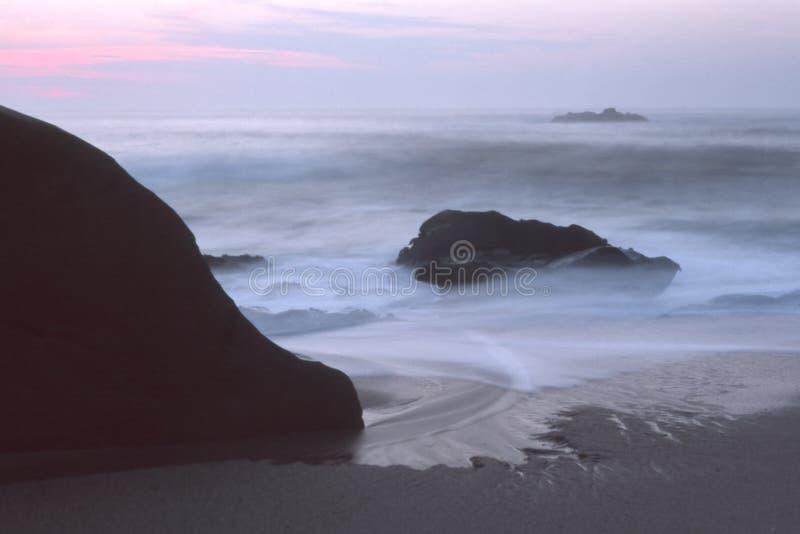 在黄昏的岩石海海滩 库存图片