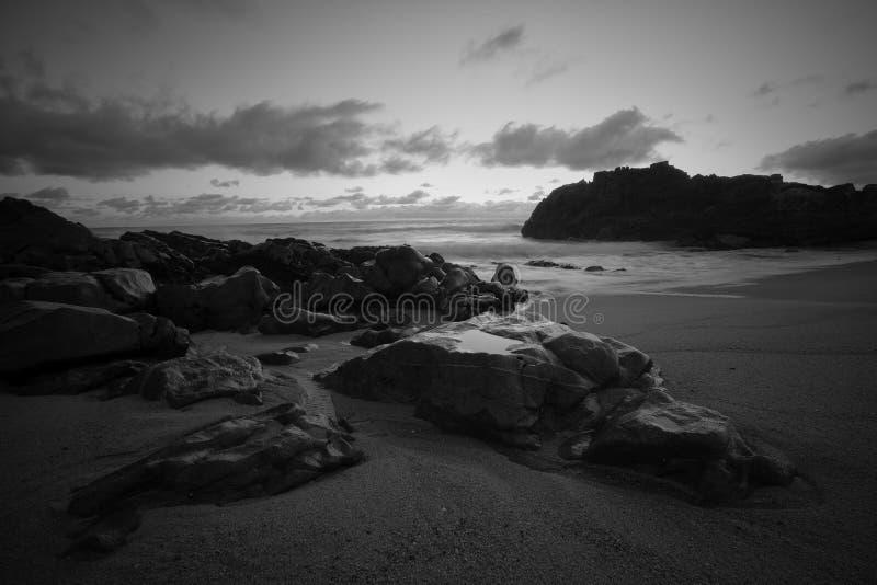 在黄昏的空的多岩石的海滩 免版税图库摄影
