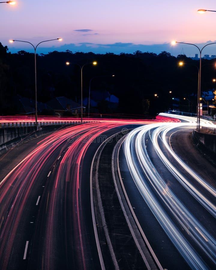 在黄昏的红灯足迹在Ryde路下,看见从太平洋高速公路桥梁在Pymble -画象 库存照片