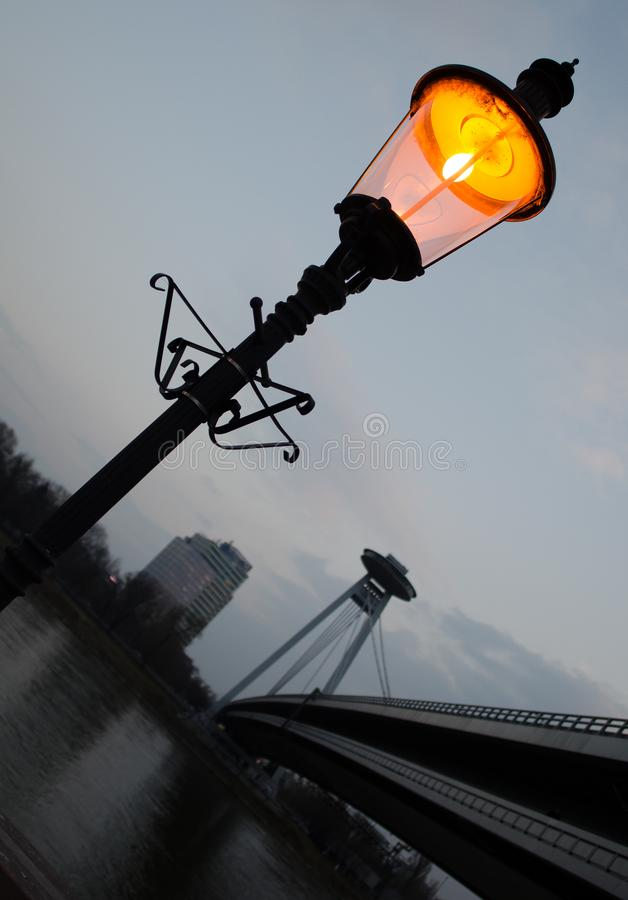 在黄昏的街灯在河附近 免版税库存照片