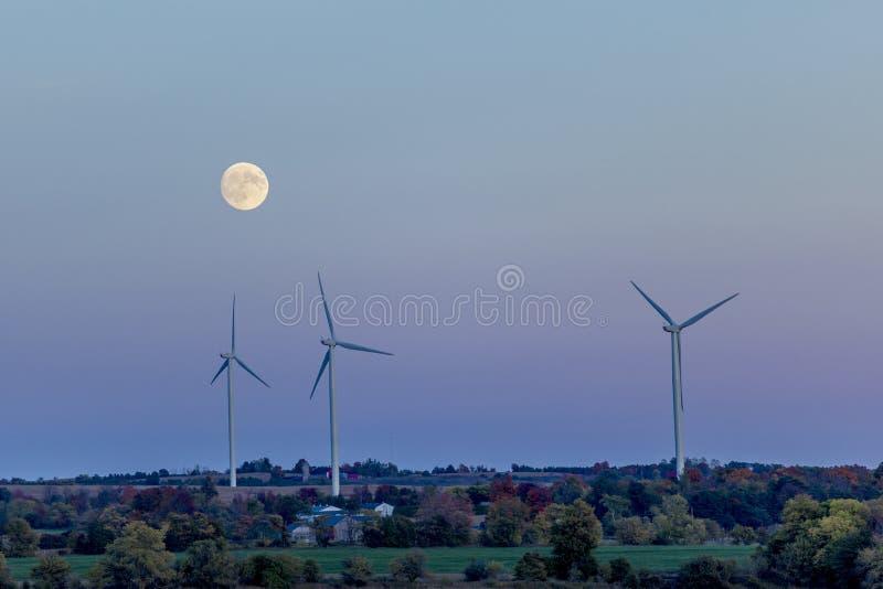 在黄昏的风轮机与满月 免版税图库摄影