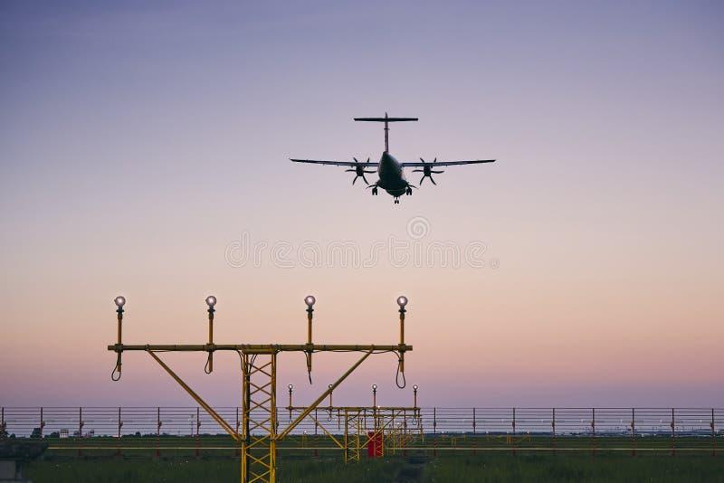 在黄昏的飞机着陆 免版税库存图片