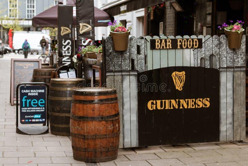 在黄柏街道上的一个典型的爱尔兰酒吧与吉尼斯标志和木头的滚磨外面 库存照片