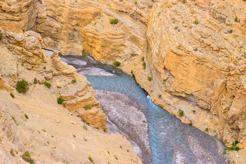 在黄沙岩石流动的蓝色河中 免版税图库摄影
