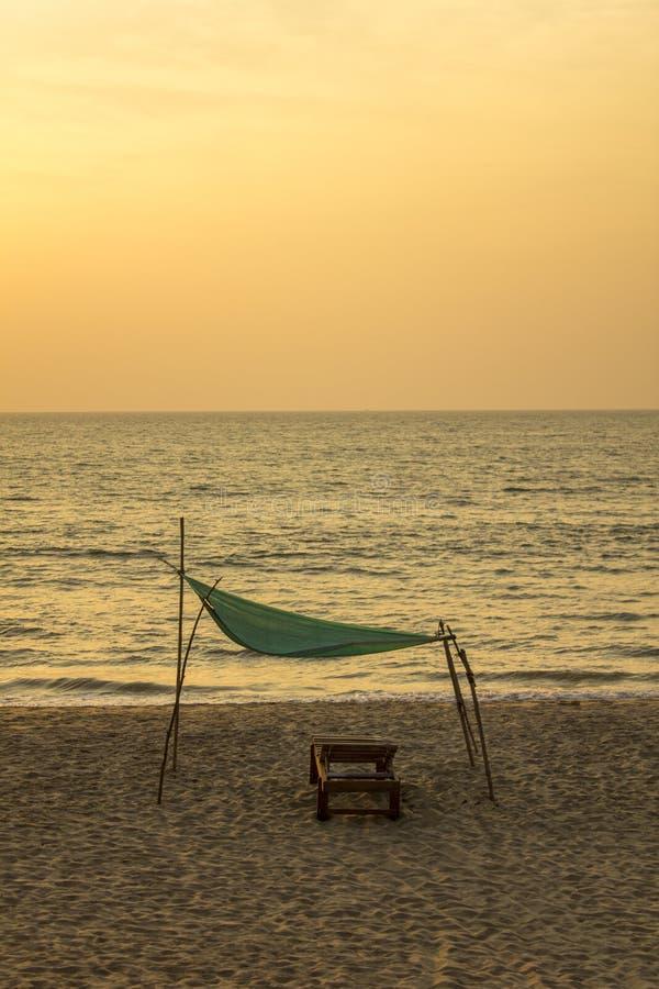 在黄沙的空的木海滩床在反对海洋和平衡的日落天空的一个绿色机盖下 免版税图库摄影