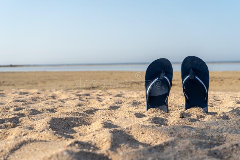 在黄沙的蓝色凉鞋触发器 夏天乐趣时间和通入 图库摄影