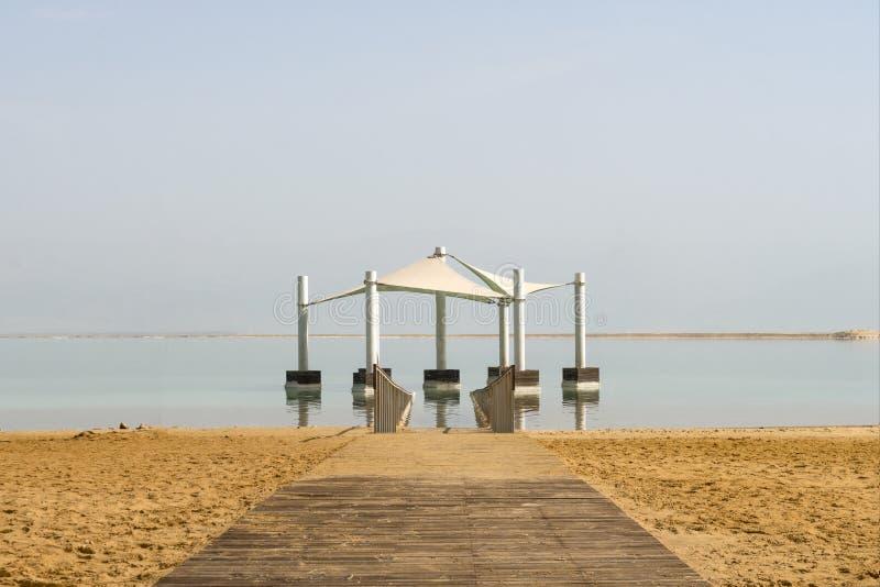 在黄沙离开的木道路在死海的距离 道路在盐水的机盖下 从太阳的机盖 免版税库存图片