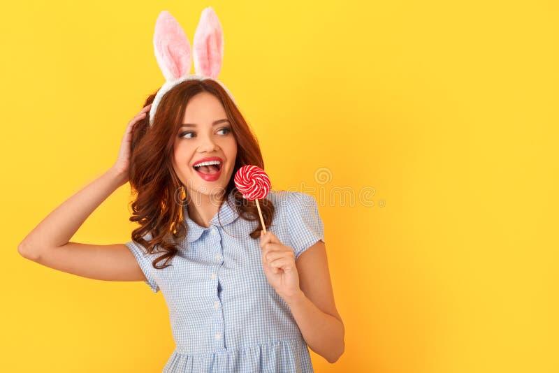 在黄色佩带的兔宝宝耳朵隔绝的少妇演播室吃看的棒棒糖在旁边 免版税库存图片