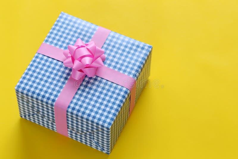 在黄色加工印刷纸地板和h安置的蓝色圣诞礼物箱子 库存照片