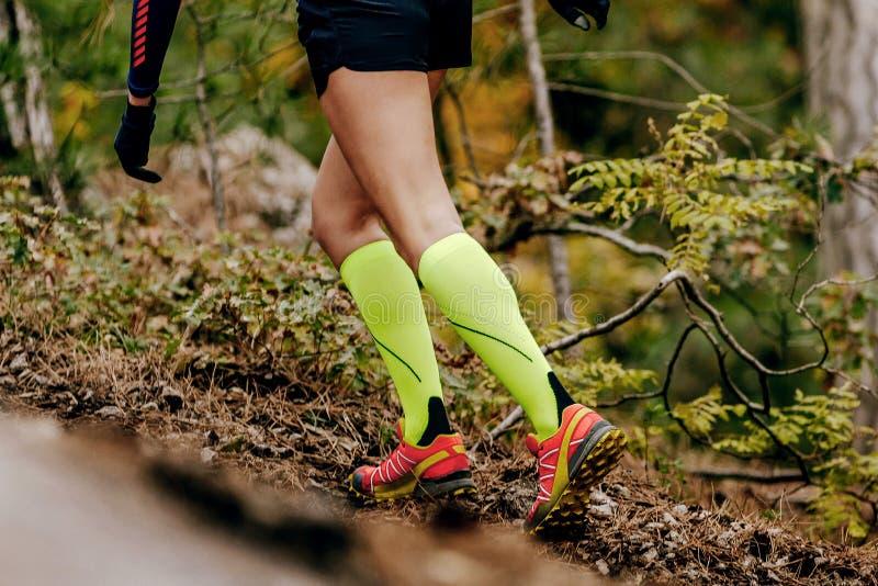 在黄色压缩袜子的母赛跑者 库存照片
