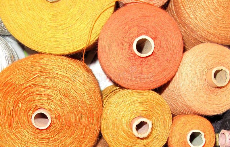 在黄色口气的编织的毛线在短管轴 库存图片