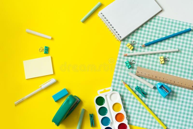 在黄色和蓝色方格的背景的学校用品 免版税库存照片